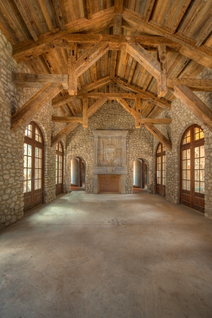 Reclaimed hand hewn timber frame stone great room