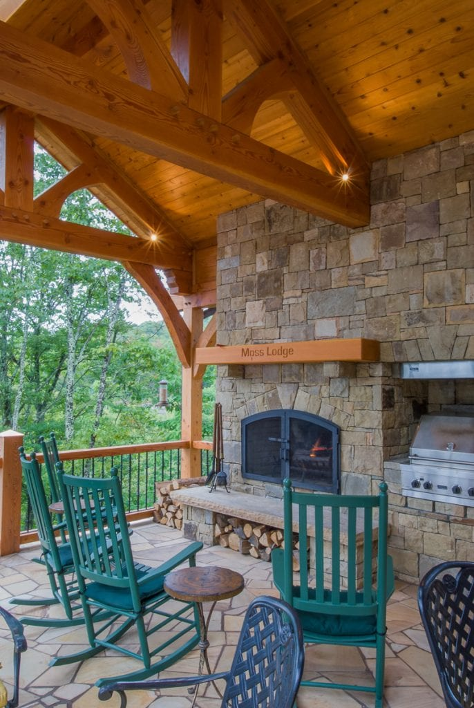 Mountain home timber frame porch with rock fireplace
