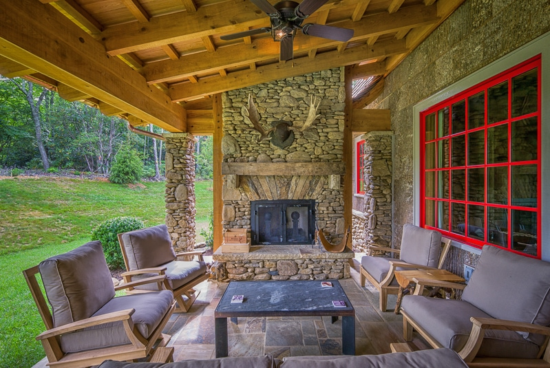 post and beam porch with outdoor fireplace and poplar bark siding