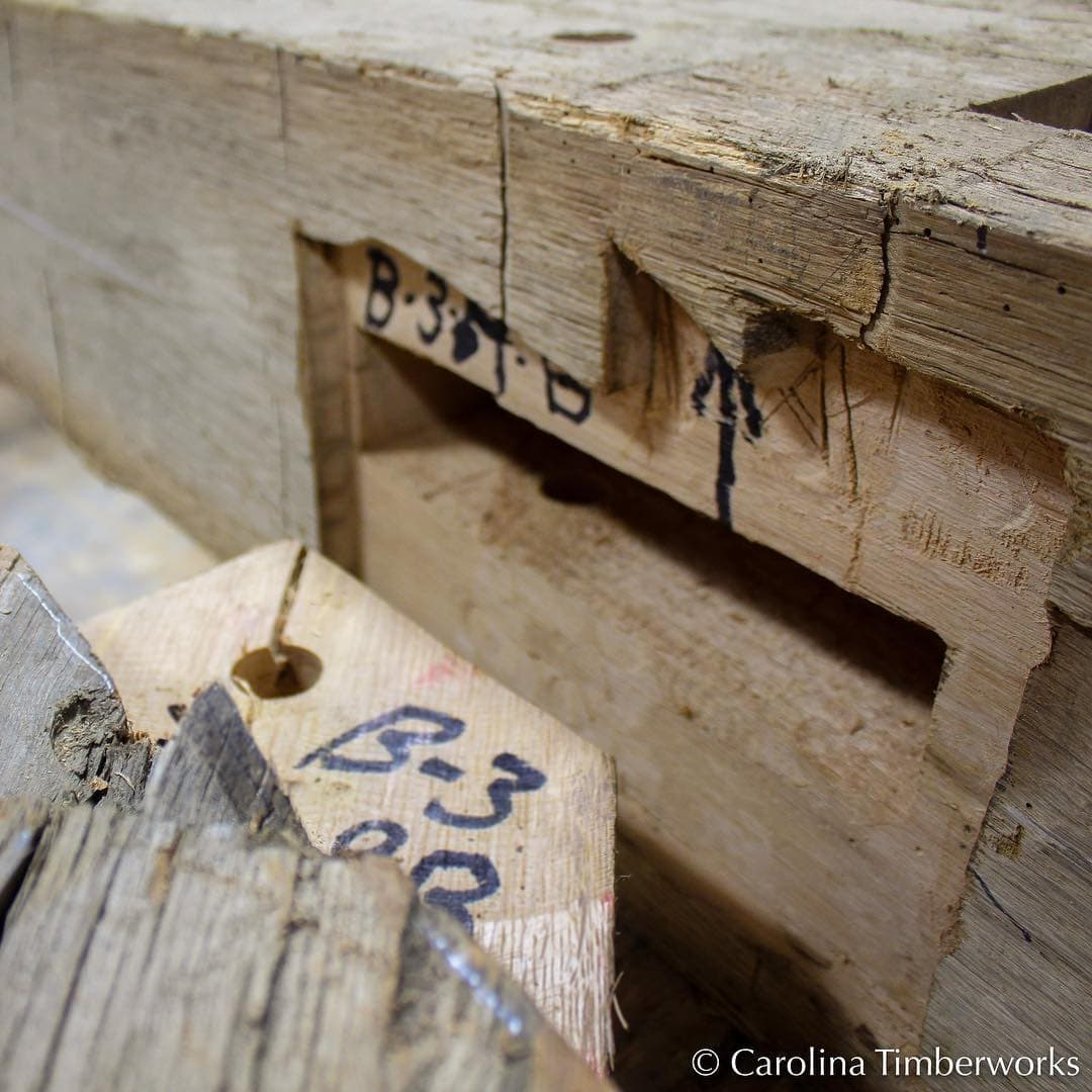 While cutting timber frame mortise & tenon joinery on new perfectly square planed smooth timbers isn't exactly child's play, scribing two un-square and irregular reclaimed beams so as to mate perfectly…is an art form.  Photo by Patricia Willis.