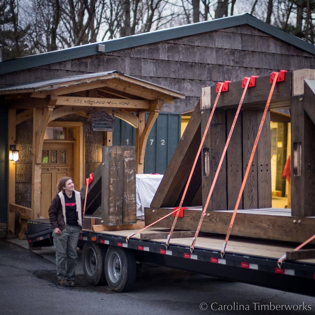 Patricia inspects and approves this load of white oak timber frame kitchen trusses. Now if only the weather would cooperate.