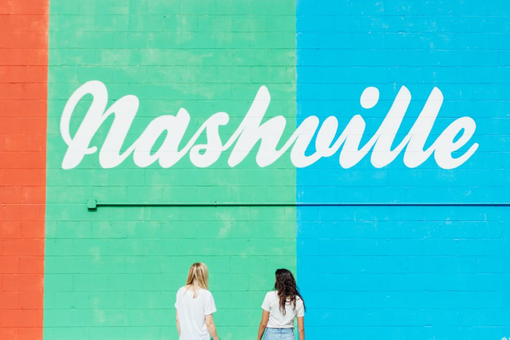 Two women standing in front of Nashville mural